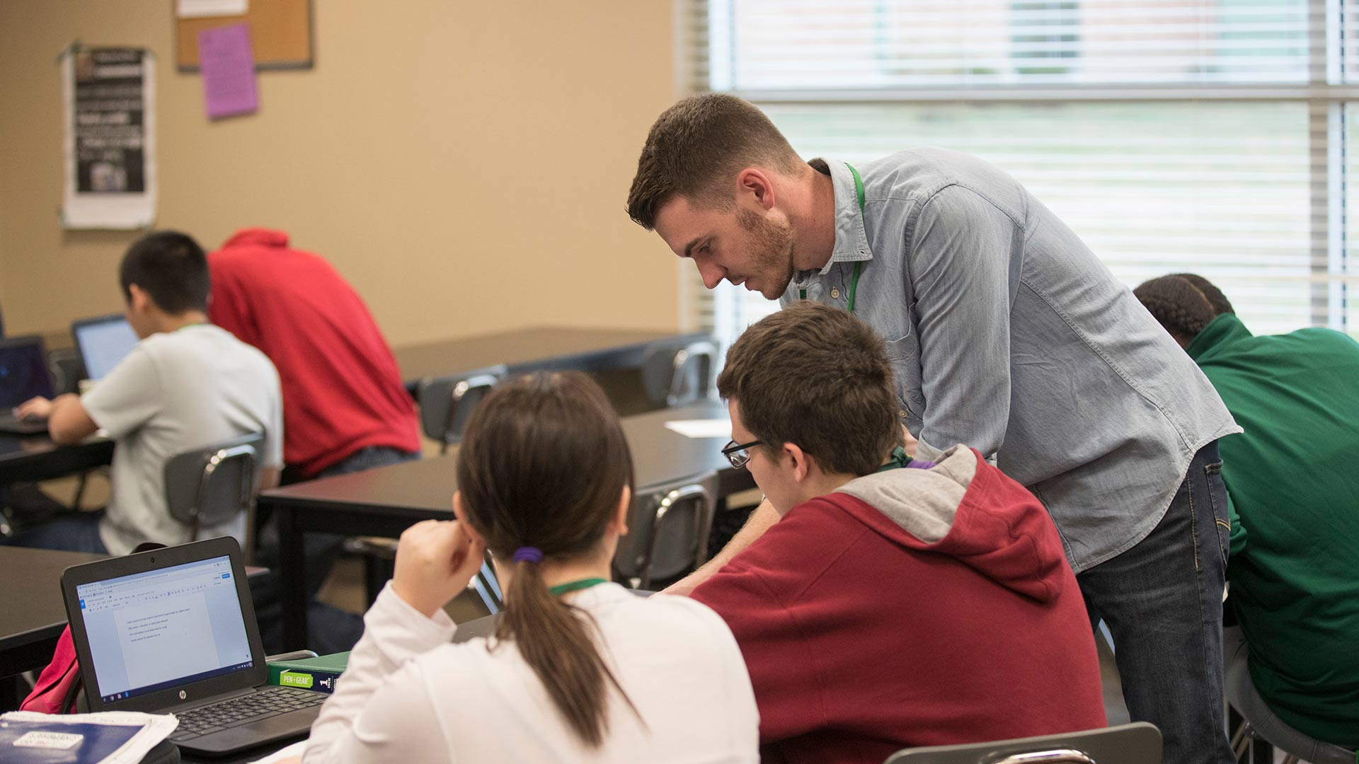 Student teacher working with students in high school classroom